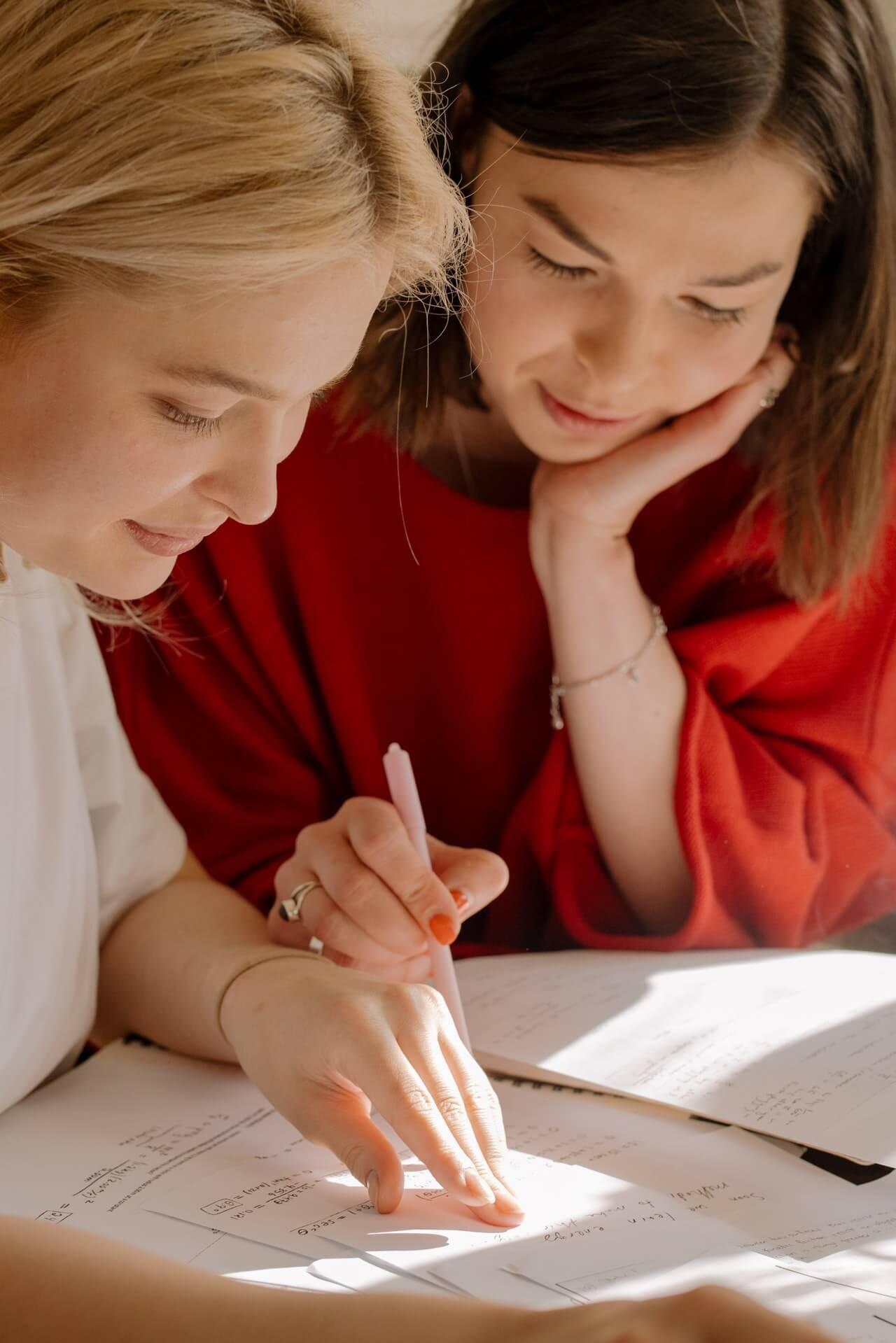 uczennica i nauczycielka odrabiające zadanie domowe