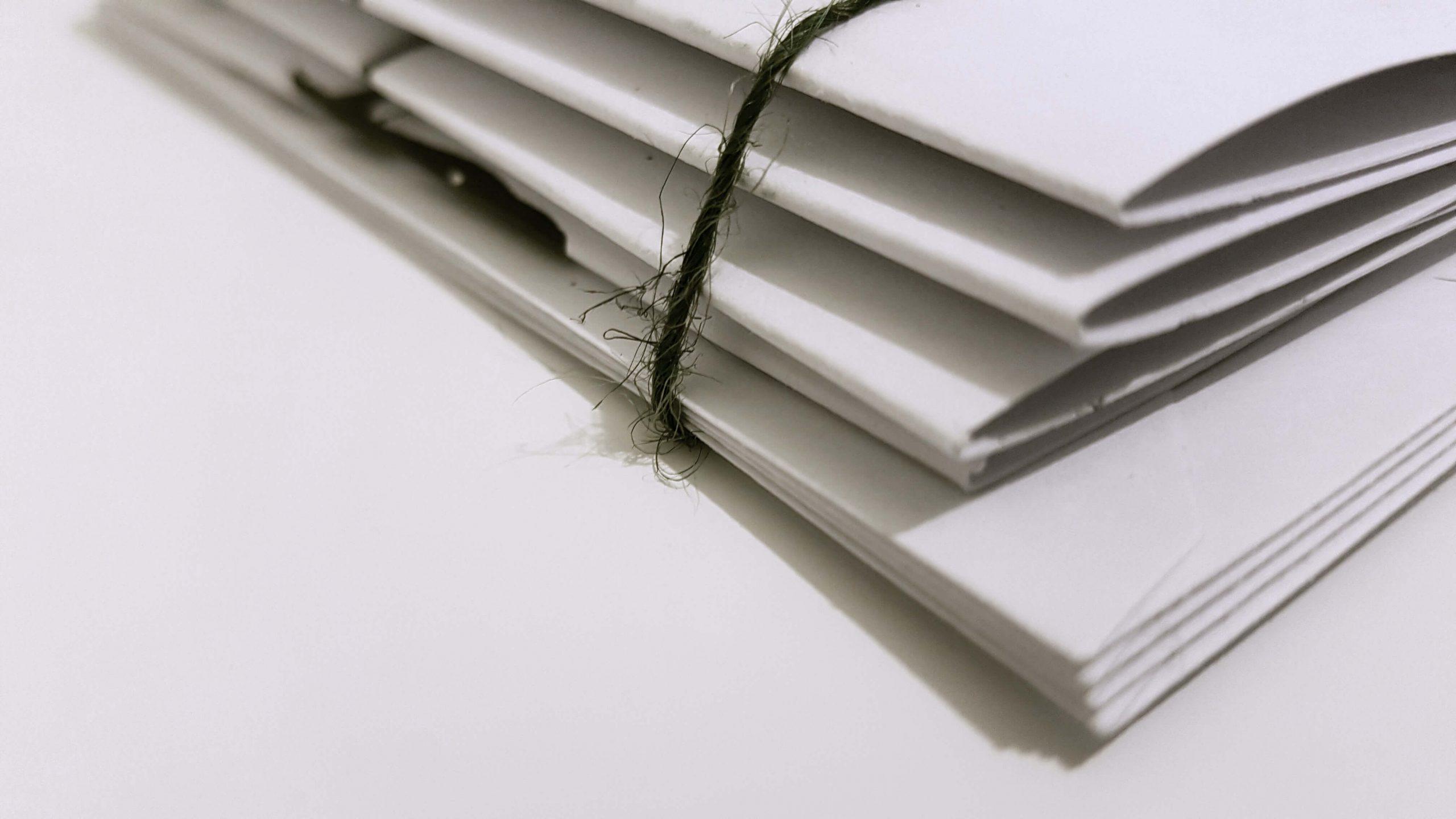 dokumenty w papierowych teczkach leżące na stole
